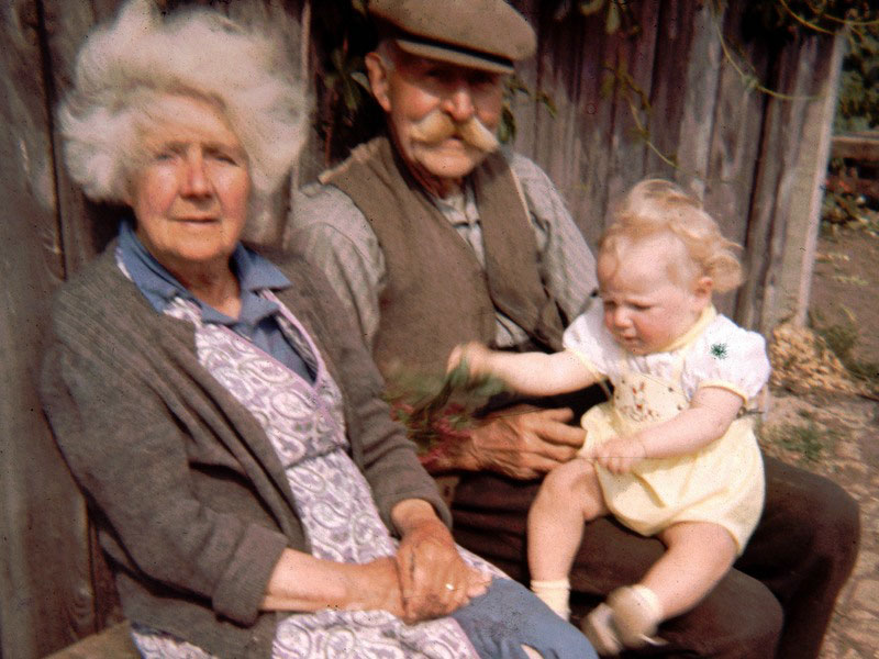 Basil Griffin ('Griffen' in list), (Lots 43 & 46) with wife and grandchild, outside his shed.