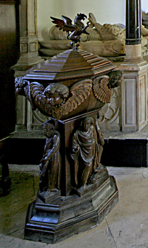 41. 17th century oak font in the chancel, with figures of saints and cherubs heads and a cover  surmounted by the Sandys griffin.