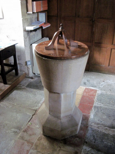47. The old stone font with a 20th century cover.