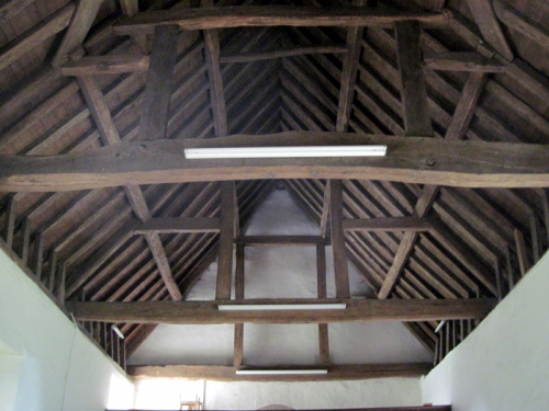 49. The queen-strut roof of the nave. The paired vertical timbers are placed symmetrically on the horizontal tie beam to  support the side purlins.