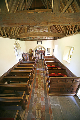 9. Pews and boxed pews, some with re-used 16th century linenfold panelling, flag stoned floor, plastered walls and queen-strut roof.