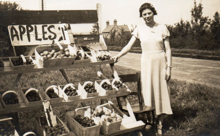 Iris Cox (b. about 1920) is at her Uncle Ernest Cox's stall. Iris remembers 13 lb of apples selling for one shilling (5p) in the mid 1930s.