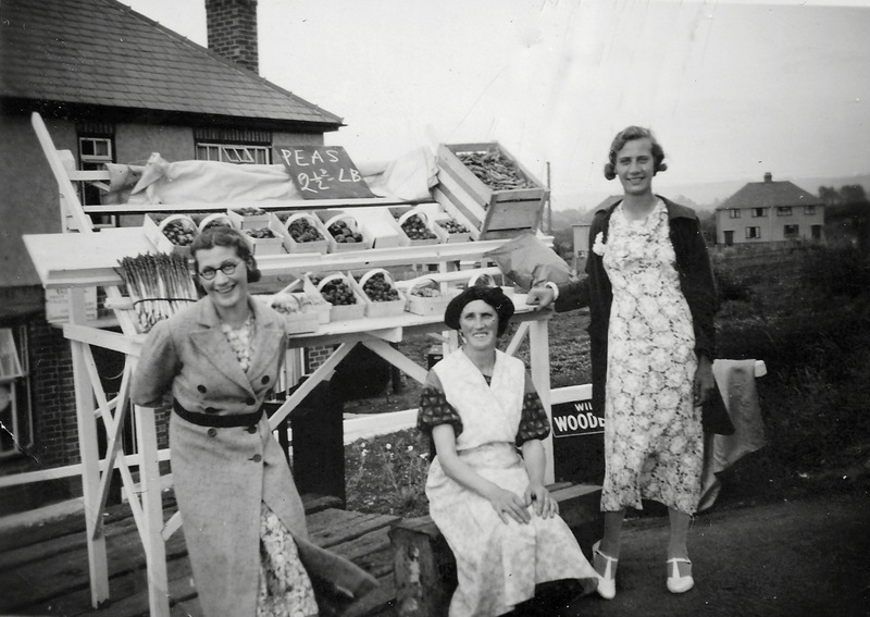 This stall was built by George Cox and put by the roadside next to his shop at 41 Pitchers Hill.   By the stall, in 1938, are pictured his wife Dorothy and daughters Dorothy (Dot), with glasses, and Ruth.