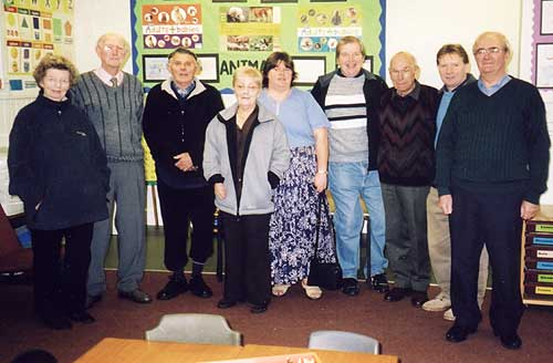 A group of former pupils and staff on a tour of the school.
