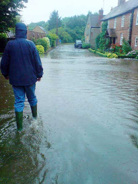 Aldington (1 of 3). Aldington Village Street was taken on Friday evening. Here the flooding is due to the quantity of rain water not getting down the drains quickly enough. The water got into at least two of the adjacent houses. Photo: Louise & John Sparrow.
