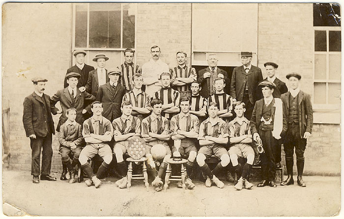 Badsey United team photo with two trophies - a shield and a cup. The man with the straw hat is Julius Sladden. Other names unknown.