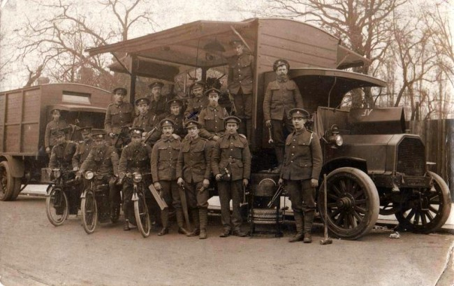 Norris Haines ( X ) with other soldiers and Army transport in France.