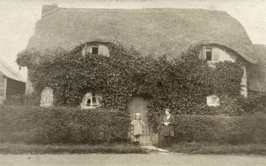 The thatched vicarage in about 1900.  The people outside have not been identified.