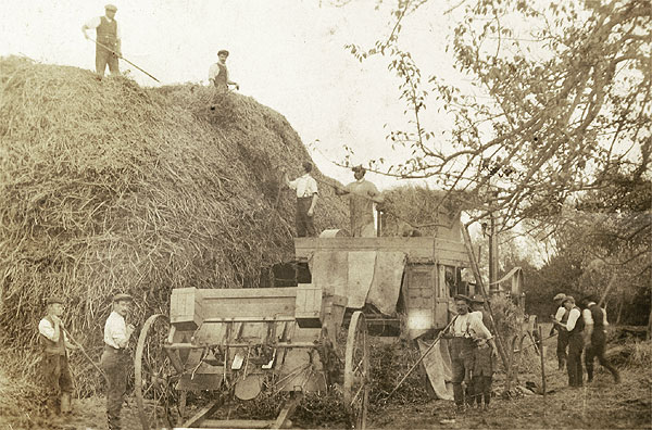 Agricultural workers bringing in the harvest with the help of some early machinery, but still a labour intensive task at about the time of the Great War