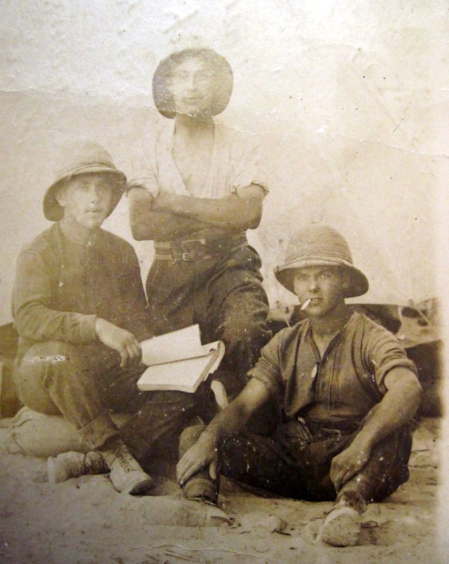 George Mason holding a book with two of his fellow soldiers in the desert at Alexandria.